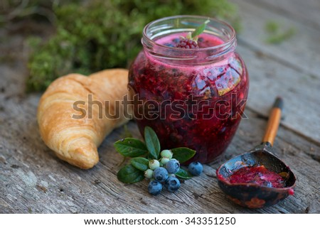 Raspberry jam and bread with butter in a jar on the wooden table Lunch breakfast  - stock photo