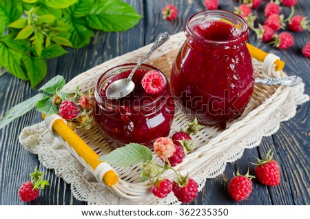 Raspberry jam and fresh raspberries on a wooden table in the garden - stock photo