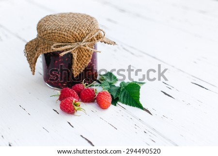 Raspberry jam in a jar on the wooden table - stock photo