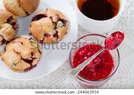 Raspberry jam in a spoon, berry muffins and black tea on white knitted tablecloth, top view - stock photo