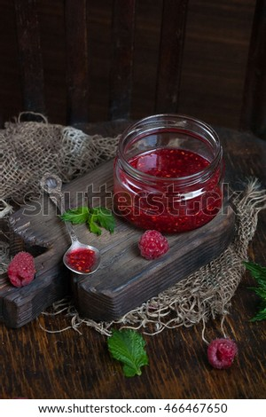 Raspberry jam. Raspberry jam ( marmalade ) and fresh raspberry on a rustic wooden table.