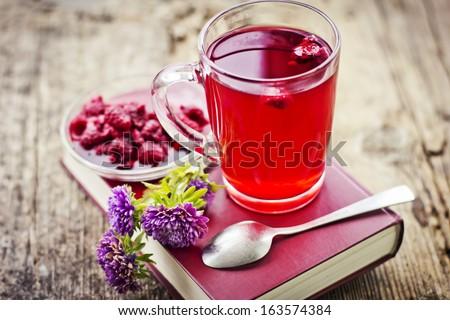 Raspberry jam tea/Romantic Autumn background with raspberry hot drink ( fruit tea) and flowers - stock photo