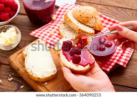 Raspberry jam to smear. Raspberry jam Woman plaster bread and butter. Jars of raspberry jam with berries on tray close up