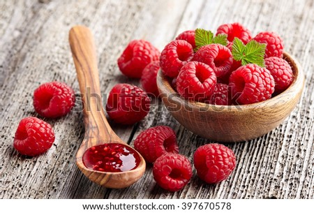 Raspberry jam with berry on a wooden background