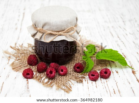 Raspberry jam with fresh berries on a wooden background - stock photo