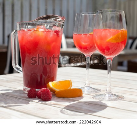 Raspberry Lemonade: two glasses, pitcher, raspberries on the table. - stock photo