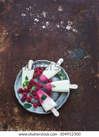 Raspberry, lime and yogurt ice-creams or popsicles with fresh berries and ice-cubes on vintage metal plate over grunge metal backdrop, top view, copy space - stock photo