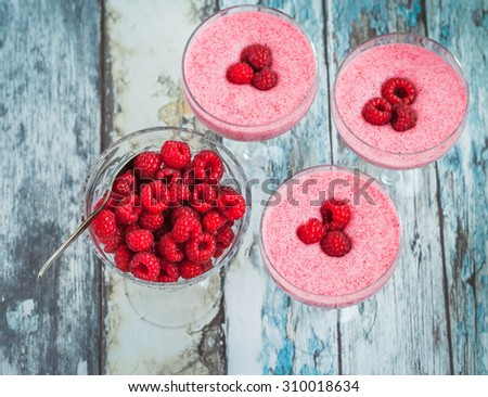 Raspberry mousse in glass on an old wooden background, top view - stock photo
