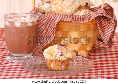 raspberry muffin on a clear glass plate with a glass mug of hot cocoa and a basket of raspberry muffins on a red checked table cloth - stock photo