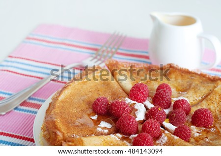 Raspberry pancakes served with sugar powder and berries
