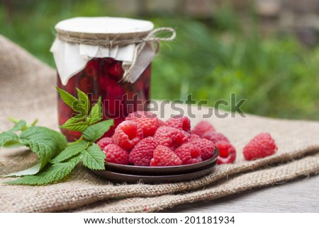 Raspberry preserve in glass jar and fresh raspberries on a plate - stock photo