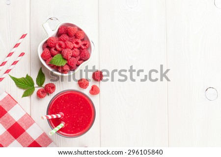 Raspberry smoothie and berries in bowl on wooden table. Top view with copy space - stock photo