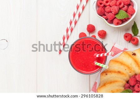 Raspberry smoothie, cake and berries on wooden table. Top view with copy space - stock photo