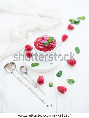 Raspberry sorbet ice-cream with mint leaves  and spoons on white background, selective focus - stock photo