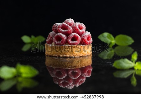 Raspberry tart dessert on dark background. Traditional french sweet pastry. Delicious, appetizing, homemade cake with custard, fresh berries and fruits. Copy space, closeup. Selective focus - stock photo