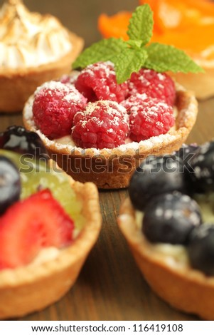 Raspberry tart, surrounded by fruity tarts  on wooden table
