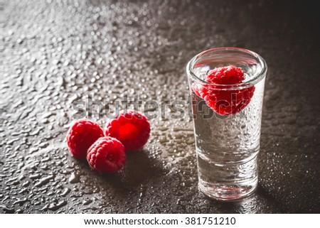 Raspberry vodka glass shot with fruit inside. - stock photo