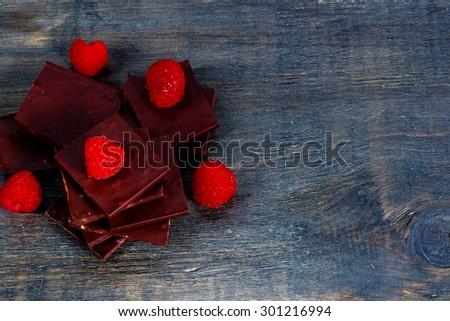 Raspberry with dark chocolate over wooden background with space for text. - stock photo