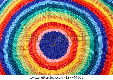 Rasta cap closeup.  Psychedelic background. Homemade knitted product. - stock photo