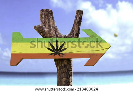 Rasta Flag With Marijuana Leaf sign with a beach on background  - stock photo