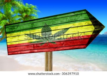 Rasta Flag With Marijuana Leaf wooden sign on beach background - stock photo