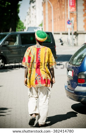 Rastaman wearing tradition al rasta hat, white pants and colorful traditional motive shirt walking on the streets of a modern city - stock photo