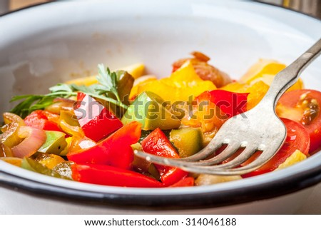 Ratatouille made of eggplant, zucchini, bell pepper and tomato and seasoned with herbs. Selective focus.