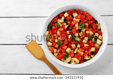 Ratatouille, stewed vegetable dish with tomatoes, zucchini, eggplant before cooking, on wooden background - stock photo