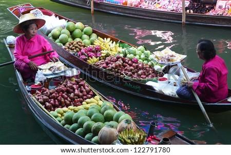 RATCHABURI, THAILAND - APRIL 26:Local vendors selling goods at Damnoen Saduak Floating Market near Bangkok in Thailand on April 26, 2010. Damnoen Saduak is a very popular tourist attraction. - stock photo