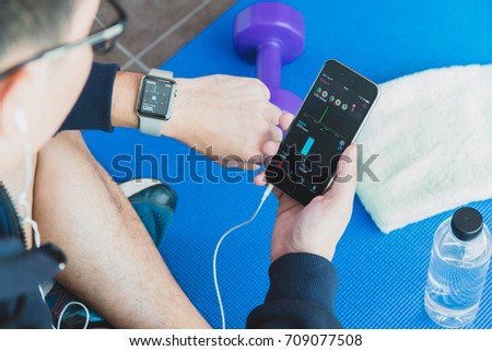 RATCHABURI, THAILAND - AUGUST 19, 2017: Asian athletes man resting after exercising. Uses a smartphone and apple watch with headphones to listen to music.
