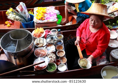RATCHABURI, THAILAND - FEB 13: A woman makes Thai food at Damnoen Saduak floating market on February 13, 2011 in Ratchaburi, Thailand. Its popular for traditional style Thai food and old Thai culture. - stock photo