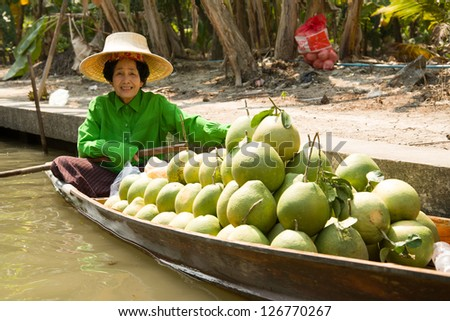 RATCHABURI, THAILAND - JAN 19: Pomelo Fruit Seller on Boat at Damnoen Saduak Floating Market on Jan 19, 2013 in Ratchburi, Thailand. The market is one of famous tourist spots in Thailand