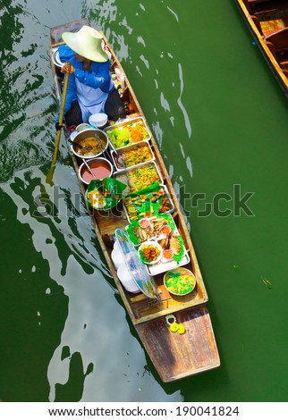 RATCHABURI, THAILAND - MARCH 24: Local peoples sell fruits, food and souvenirs at famous tourist attraction Damnoen Saduak floating market on March 24, 2014 in Ratchaburi, Thailand. - stock photo