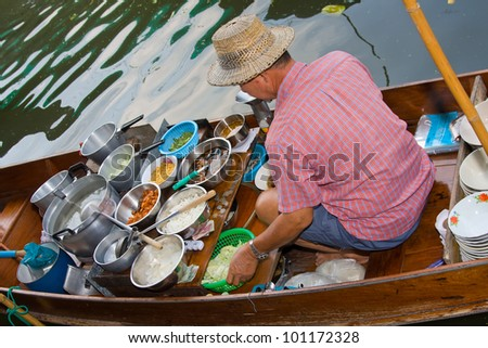 RATCHABURI, THAILAND - NOV 30: A men makes Thai food at Damnoen Saduak floating market on November 30, 2011 in Ratchaburi, Thailand. Its popular for traditional style Thai food and old Thai culture. - stock photo