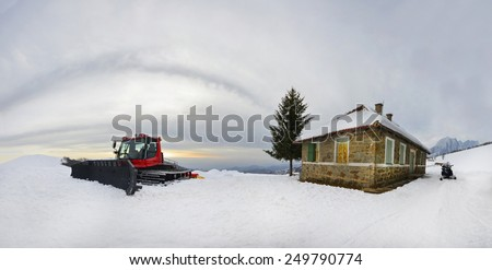 Ratrac Tractor on cleaning snow ski slope outdoors. Mountain landscape panorama