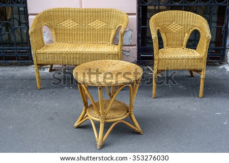 Rattan chairs and table on the street - stock photo