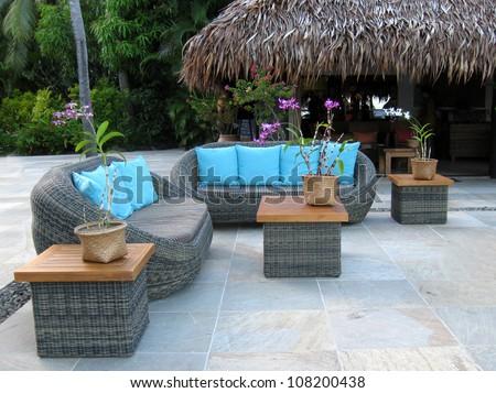 rattan furniture in tropical setting - stock photo