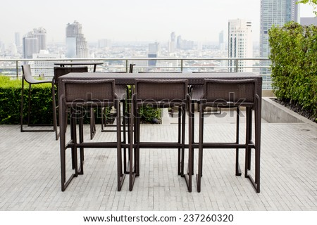 Rattan oone table with two stool chairs standing against the terrace - stock photo