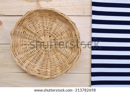 Rattan plate or basket on wooden table and tablecloth on table wood plank made for background - stock photo