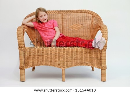 rattan sofa and relaxing girl - stock photo