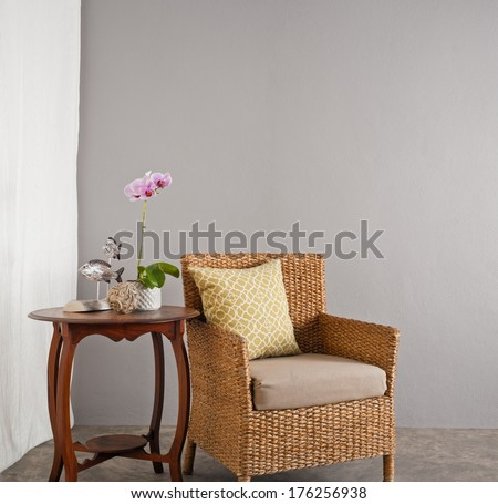 Rattan sofa chair in a patio garden lounge setting - stock photo