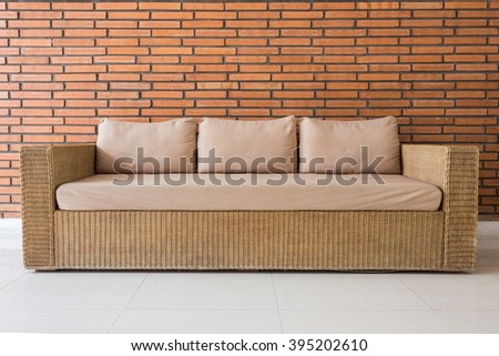 Rattan sofa with grey cushions and red brick wall background - stock photo