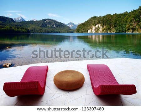 Rattan sunbeds on the white floor with mountains and lake - stock photo