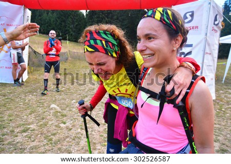 "rausor, romania - august 1, 2015: two women crossing the finish line at the trail running race ""retezat marathon""  in rausor, romania - retezat national park. shot taken on august 1st, 2015"