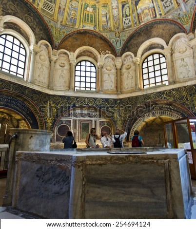 RAVENNA, ITALY -SEPTEMBER 6, 2014: People inside the Baptistery of Neon in Ravenna, Italy, with the baptismal font in the foreground. - stock photo