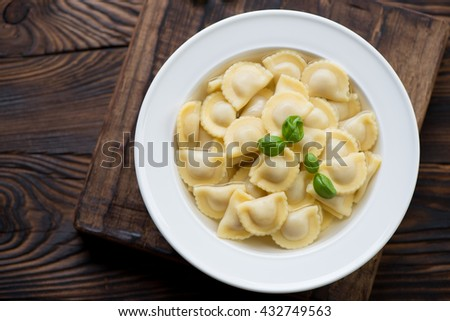Ravioli in bouillon, top view, rustic wooden background