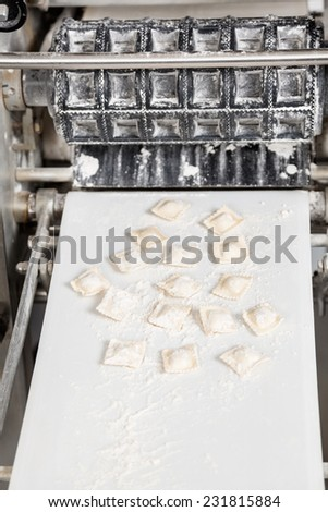 Ravioli pasta on automated machine in commercial kitchen - stock photo