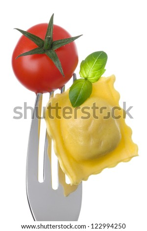 ravioli pasta tomato and basil on a fork against white background