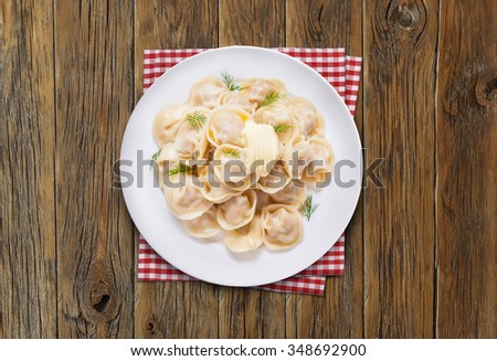 Ravioli pasta with sauce and fresh herbs. Top view on wooden table.  - stock photo