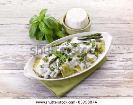 ravioli stuffed with ricotta and basil garnish with cream and asparagus - stock photo